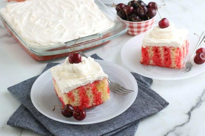 Cherry topped cakes on white plates.
