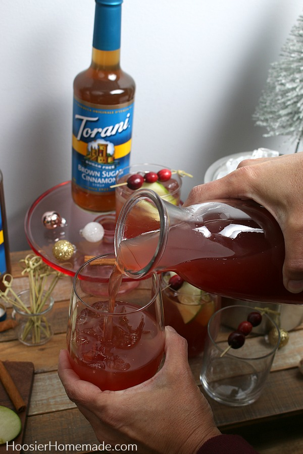 Pour cranberry and apple juice into glass