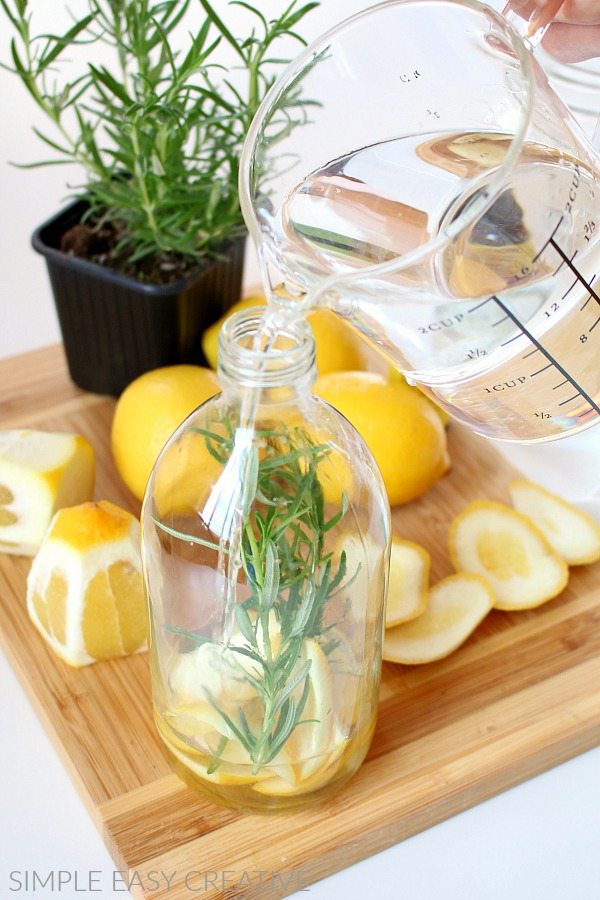 Pour vinegar, water and essential oil cleaning solution into glass bottle.