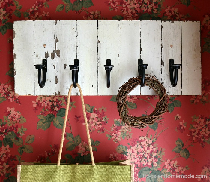 DIY COAT RACK -- This easy to make Farmhouse Coat Rack uses old barn wood and curtain tie backs! Build this coat rack for under $25!