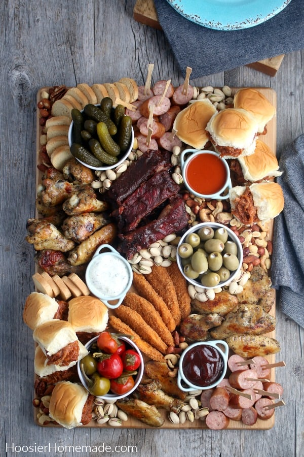 Board with meat snacks pickles olives peppers
