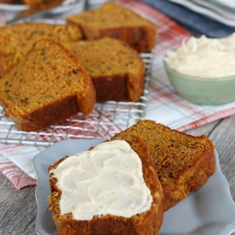 Pumpkin Bread sliced on gray plate with cinnamon butter